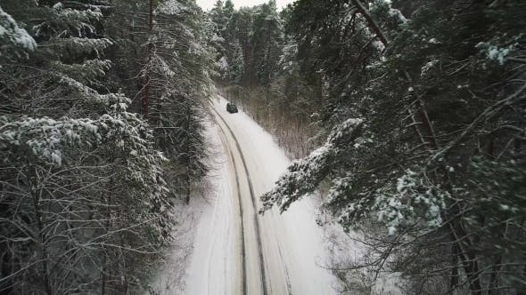 Cover Image for Aerial View of Car Moving in Winter Forest