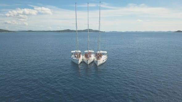 Cover Image for Three Sailing Yachts Are Connected, Near Beautiful Islands. Beautiful Clouds
