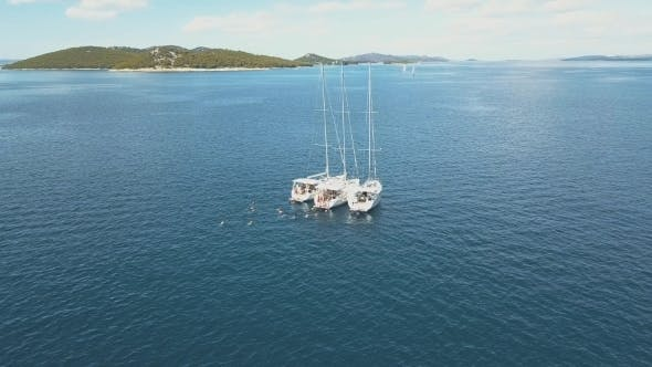 Cover Image for Three Sailing Yachts Are Connected, Near Beautiful Islands. Beautiful Clouds in the
