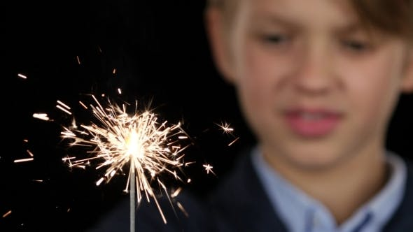 Thumbnail for Boy Is Holding a Sparkler in His Hand on Black Background