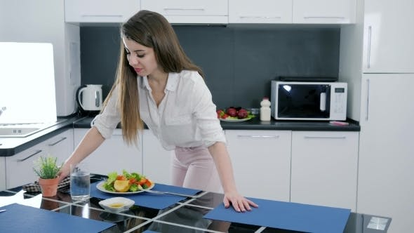 Cover Image for Young Woman Is Cleaning From Kitchen Table After Cooking Salad at Home