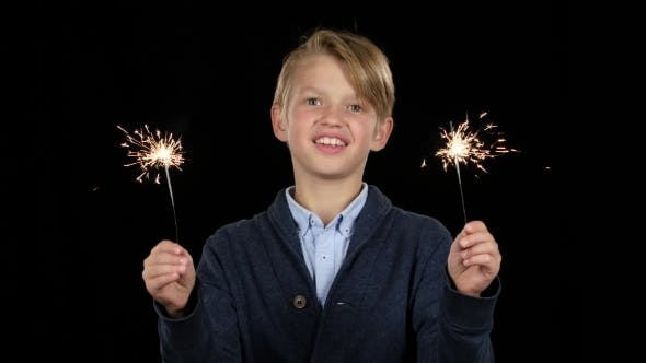Thumbnail for Boy Holds a Bengal Fire in Both Hands Smiling on Black Background