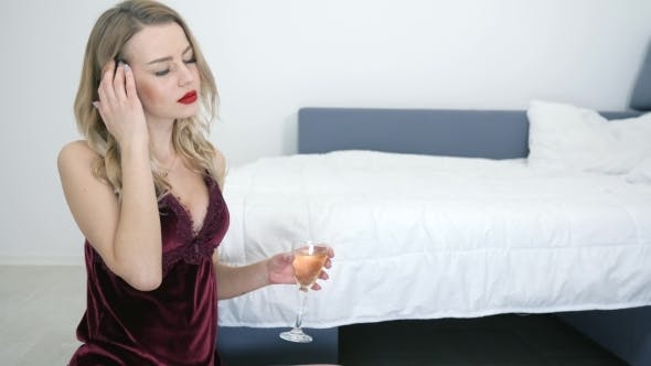 Thumbnail for Tired Blonde Having Headache in Sexy Nightie Holds Glass with Champagne Sitting Near Bed on Floor in
