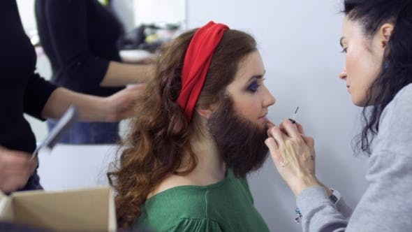 Thumbnail for Stylists Sticks Artificial Beard on Girl's Face, Dressing Room in Theatre