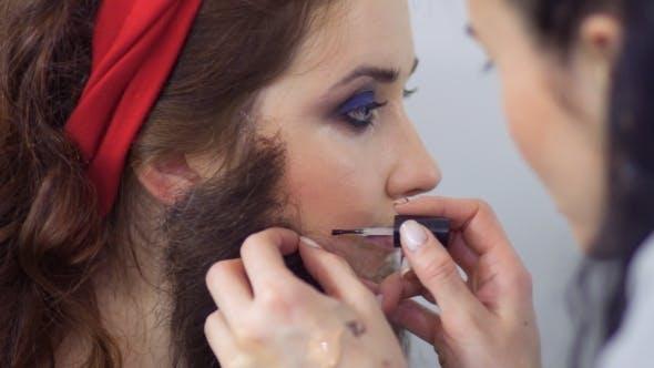 Thumbnail for Professionelle Stylistin schafft einen szenischen Charakter für junge Schauspielerin