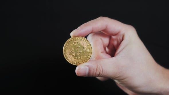 Thumbnail for Mannes Hand hält Goldene Bitcoin auf schwarzem Hintergrund Litecoin Ethereum Neo