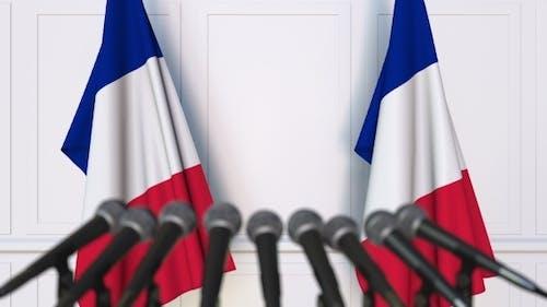 Offizielle französische Pressekonferenz mit Flaggen Frankreichs