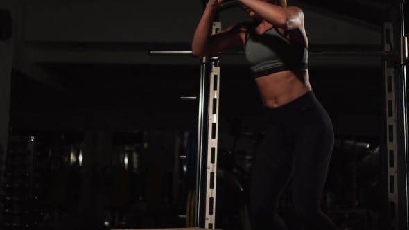 Cover Image for Beautiful Female Fitness Athlete Performs Box Jumps in a Dark Gym Wearing Black Sports Top and Short