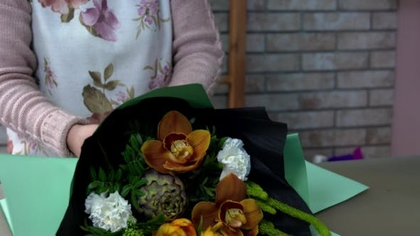 Thumbnail for Florist Wraps a Bouquet in Green Wrapping Paper. Artichoke, Orange Orchid, White Carnation