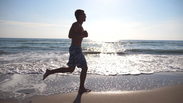 Thumbnail for Young sporty man running on the sea beach at morning. Athletic guy jogging along coast on sunny day