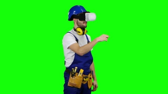Thumbnail for Engineer in Virtual Reality Glasses Builds Graphics in a Fictional Table on Green Screen