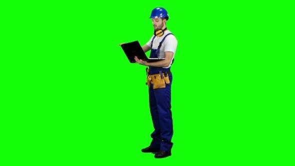 Thumbnail for Foreman mit einem Laptop sagt, wie man ein Gebäude auf Green Screen baut