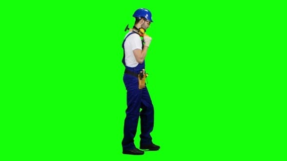 Thumbnail for Man Builder with a Hammer in His Hands Goes to the Construction Site on Green Screen