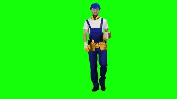 Thumbnail for Builder in a Helmet Goes to Work with Wooden Boards in His Hands on Green Screen