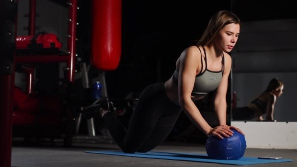 Thumbnail for A Brunette Athletic Builds Push-ups on a Mache in the Gym Putting a Stopwatch on the Mobile Phone