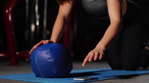Thumbnail for A Brunette Athletic Builds Push-ups on a Mache in the Gym