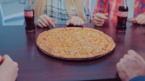 Hungrige Freunde nehmen Stücke von Käse-Pizza