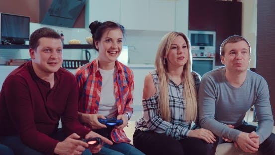Happy Couples in Love People Enjoy Relaxing By Playing Videogames with Wireless Controllers and