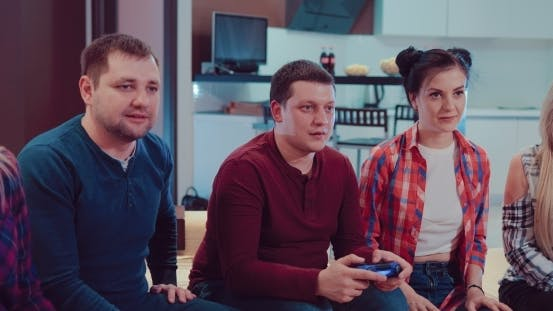 Happy Group of Laughing Male and Female Friends Playing Video Games with Wireless Controllers