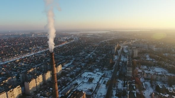 Aerial Shot of Huge Boiler Tube with Dense Smoke in European City at Sunset