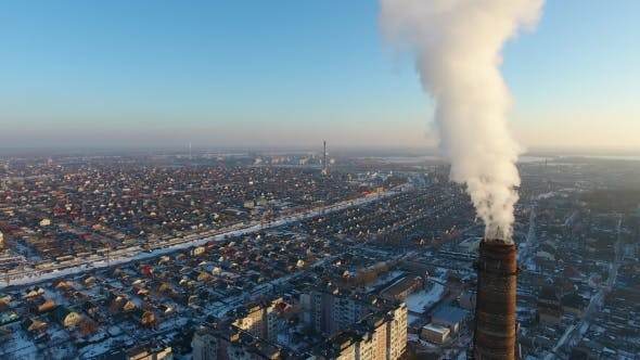 Aerial Shot of Colossal Heating Chimney with Dense Smoke in Snowy City in Winter