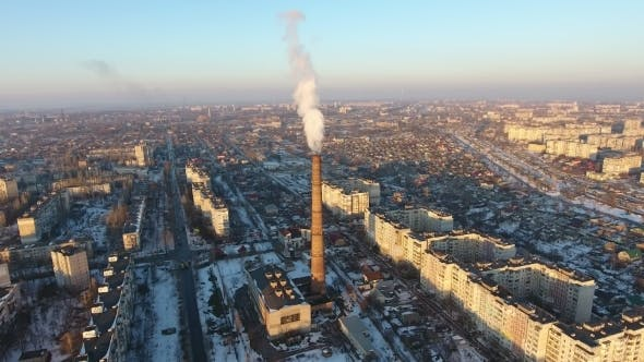 Aerial Shot of High Boiler Tube with Dense Smoke in European City at Sunset