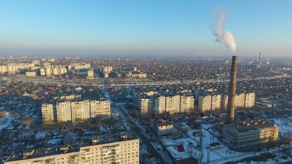 Aerial Shot of Huge Heating Chimney with Dense Smoke in Snowy City in Winter