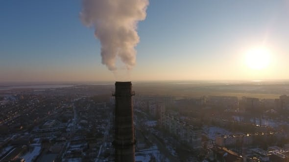 Thumbnail for Aerial Shot of Immense Chimney with White Smoke in Snowy City at Sunset in Winter