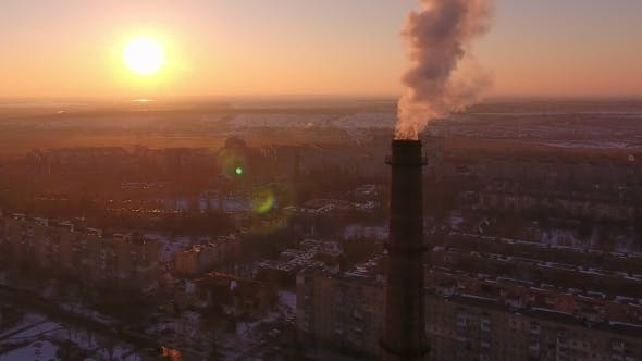 Aerial Shot of High Brick Tube with Smoke Stream in Ukrainian City at Sunset