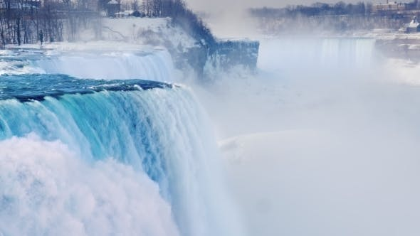 Thumbnail for Magnificent Niagara Falls in Winter. Streams of Water Fall Down Against the Background of a Snow