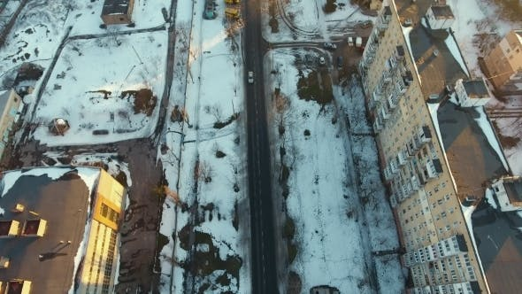 Thumbnail for Aerial Shot a Snowy Street with Moving Cars on It Among Multistireyed Buildings