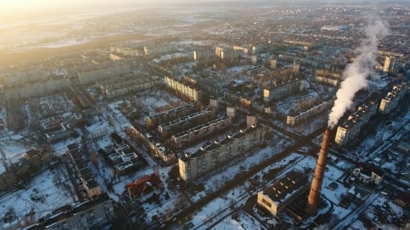 Thumbnail for Aerial Shot of High Boiler Chimney with Dense Smoke in European City at Sunset