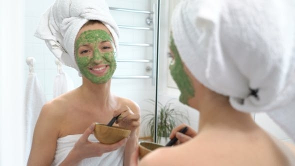 Thumbnail for Young Woman with a White Towel Put on Her Face a Green Moisturizing Mask