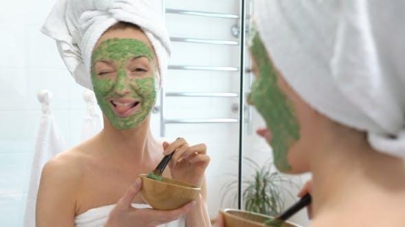 Thumbnail for Junge Frau mit einem weißen Handtuch setzen Sie auf Ihr Gesicht eine grüne Feuchtigkeitsmaske