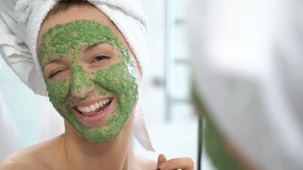 a Young Woman with a White Towel Put on Her Face a Green Moisturizing Mask
