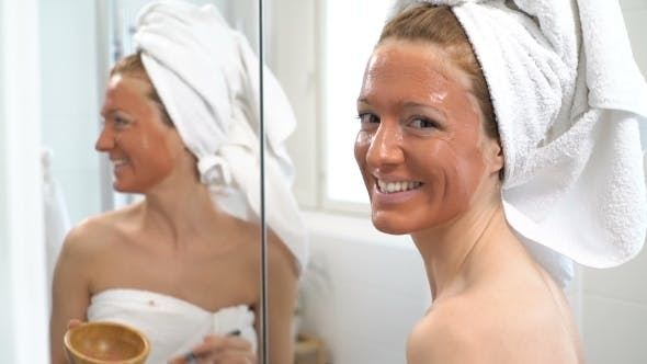 Thumbnail for a Young Woman with a White Towel Put on Her Face a Brown Moisturizing Mask