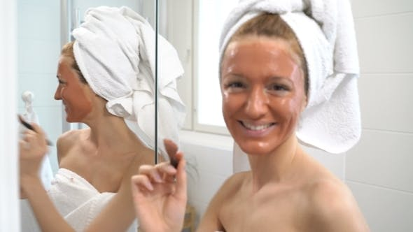 Thumbnail for Young Woman with a White Towel Put on Her Face a Brown Moisturizing Mask