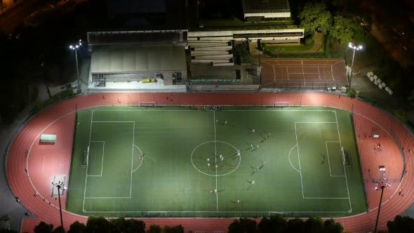Cover Image for Aerial Shot of Modern Football Field with Playing Athletes in Paris at Night