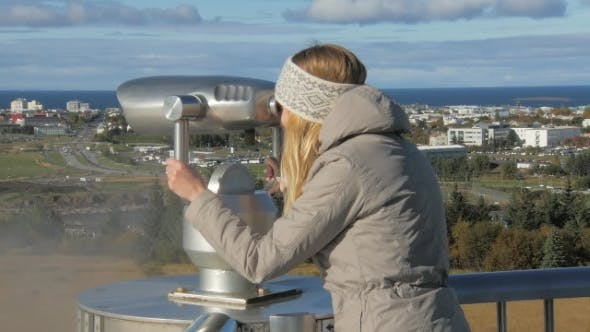 Thumbnail for Young Tourist Girl Is Looking in a Stationary Telescope on Reykjavik in Sunny Day