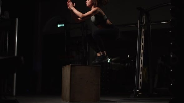 Thumbnail for Beautiful Female Fitness Athlete Performs Box Jumps in a Dark Gym Wearing Black Sports Top and Short