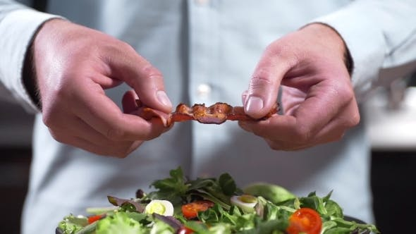 Thumbnail for The Cook Breaks a Crisp Piece of Bacon, Chef Cooks Salad with Pieces of Fried Bacon, Cooking Meat
