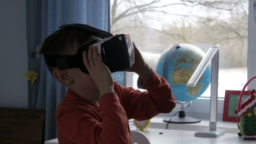 Boy in Virtual Reality Glasses Watching 360 Degree Video