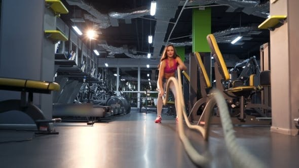 Thumbnail for Girl Is Doing Exercises Using Sports Equipment Rope. Battle Rope Exercise at Gym