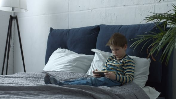 Thumbnail for Adorable Boy Using Smart Phone Playing on Line