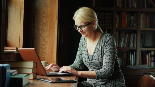 Cover Image for Business Woman Working with Laptop. Sits By the Window in the Office