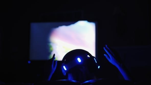 Thumbnail for A Woman Is Playing in the Helmet of Virtual Reality. Late in the Evening at Home, in the Hands Holds