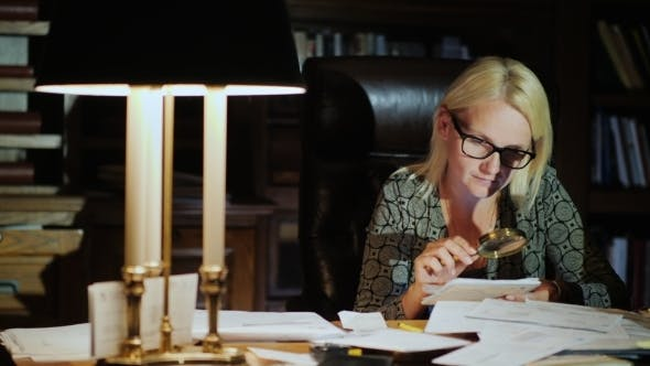 Thumbnail for A Woman Is Studying Business Papers, Looking Carefully Through a Magnifying Glass