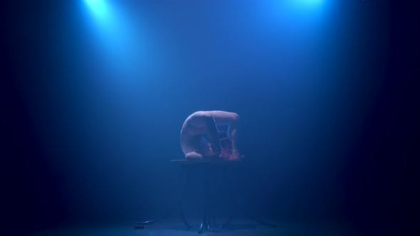 Thumbnail for Acrobat on Stage Standing on the Table Raises but Up on Vertical Twine. Smoke Blue Background