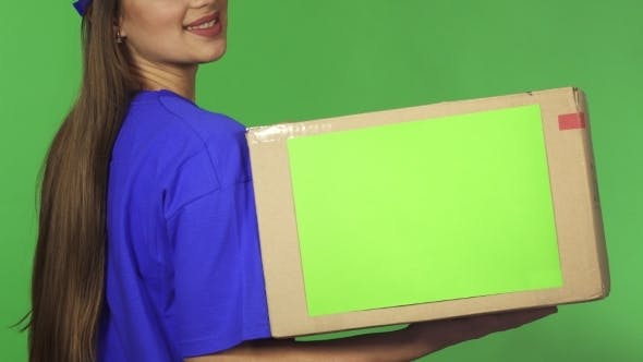Thumbnail for Cropped Rearview Shot of a Smiling Delivery Woman Holding Cardboard Box