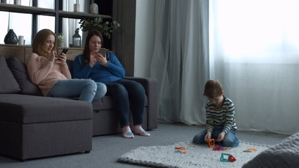 Thumbnail for Attractive Women Relaxing on Couch with Smartphones